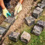 Wegebau - Steine werden ordendlich im Boden plaztiert